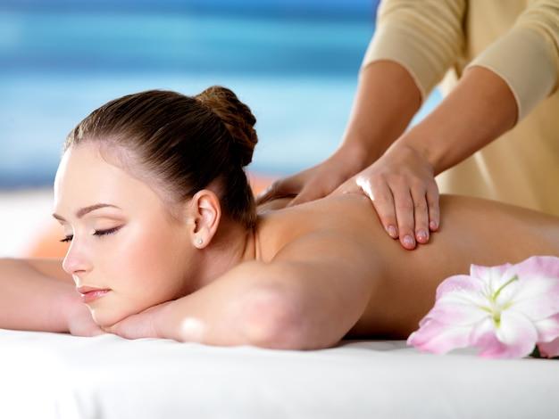 Linda jovem no salão de beleza recebendo massagem no spa Foto gratuita