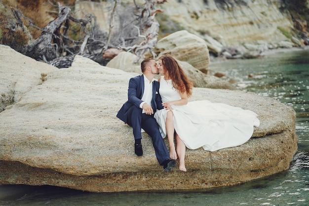 Linda jovem noiva cabelos compridos em vestido branco com seu jovem marido perto do rio Foto gratuita