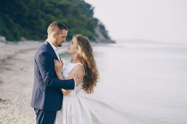 Linda jovem noiva cabelos longos em vestido branco com seu jovem marido na praia Foto gratuita