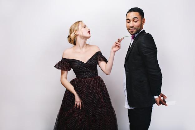 Linda jovem num vestido de noite com flor, olhando travessamente para o homem bonito de smoking com presente nas costas. casal adorável brincalhão, dia dos namorados, surpresa. Foto gratuita
