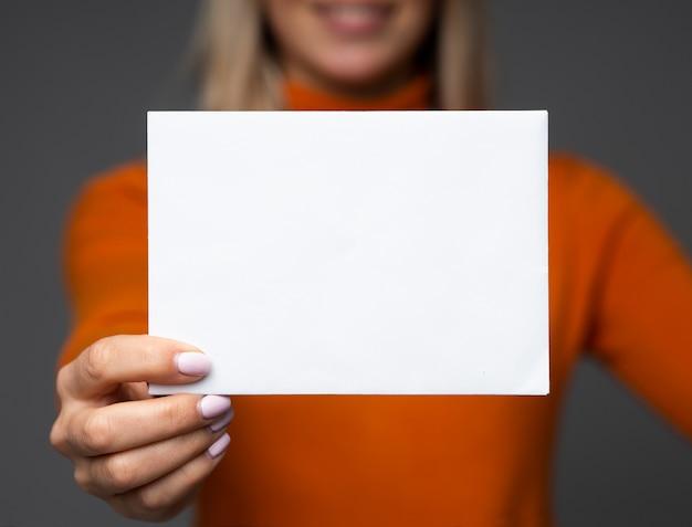 Linda jovem segurando uma folha de papel branco Foto Premium