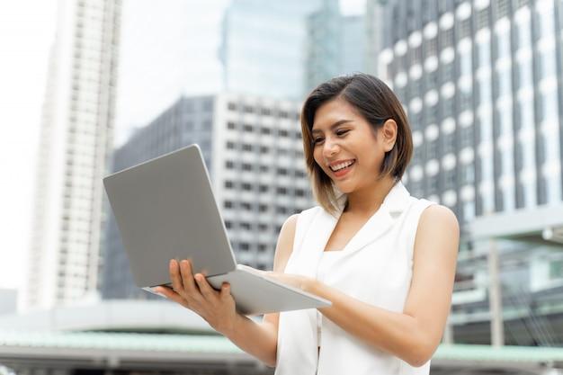Linda linda garota sorrindo em roupas de mulher de negócios usando o computador portátil Foto gratuita