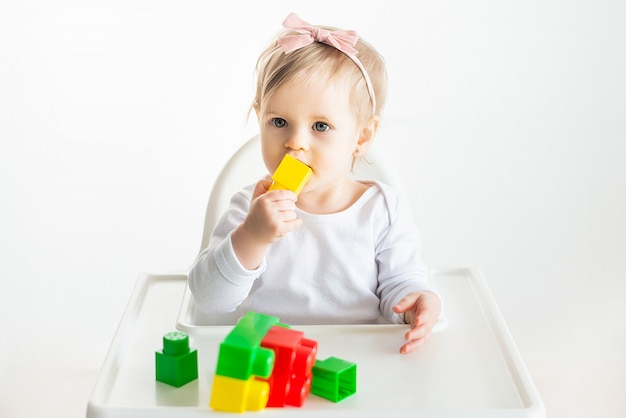 Linda loira bebê desfrutando de brincar com brinquedos no jardim de infância, mostra mão de berçário em blocos coloridos. jogando criança isolatd em fundo branco Foto Premium