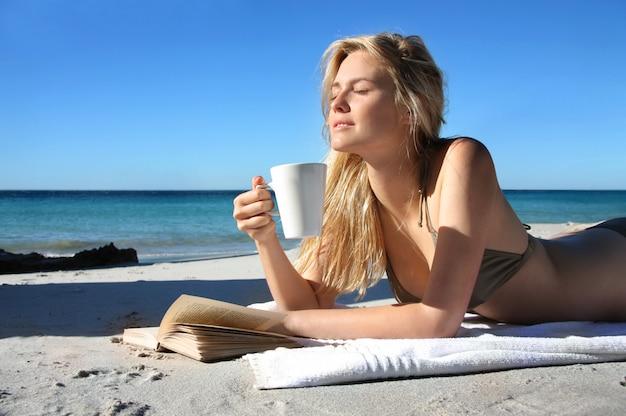 Linda loira bebendo uma xícara de café e lendo um livro na praia Foto Premium