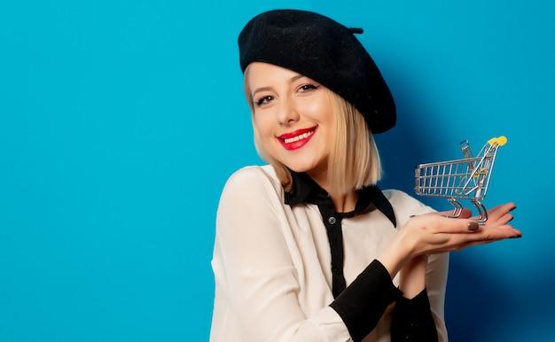 Linda loira com carrinho de compras na parede azul Foto Premium