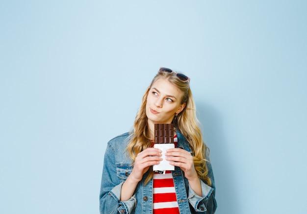 Linda loira comendo chocolate está animado sobre um fundo azul Foto Premium