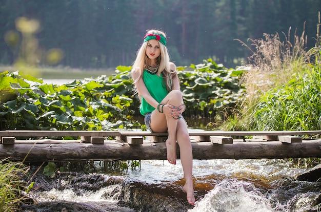 Linda loira em shorts e bandana de pé Foto Premium
