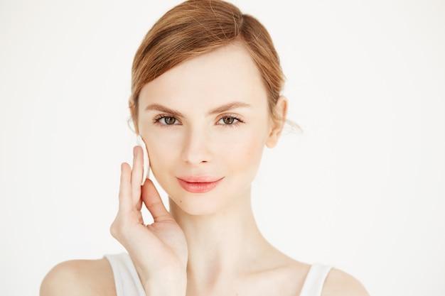 Linda loira loira limpeza rosto com algodão esponja sorrindo. cosmetologia e spa. Foto gratuita