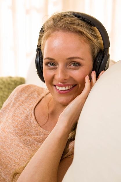 Linda loira, ouvindo música com fones de ouvido sentado no sofá Foto Premium