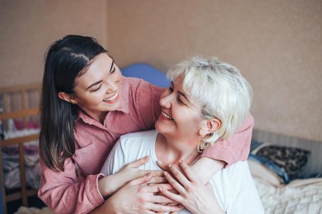 Linda madura loira mãe e sua filha adulta morena estão abraçando Foto Premium