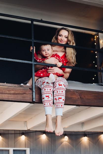 Linda mãe com filha em pijama de natal lendo livro na cozinha. Foto Premium