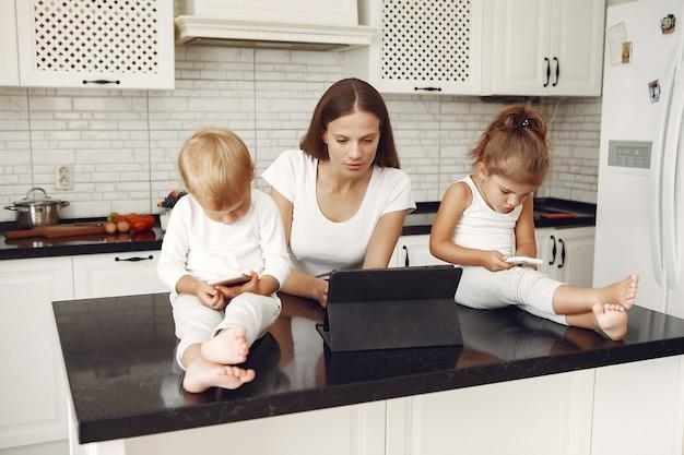 Linda mãe com filhos bonitos em casa em uma cozinha Foto gratuita