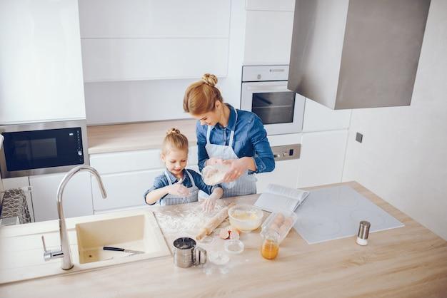 Linda mãe de camisa azul e avental está preparando o jantar em casa na cozinha Foto gratuita