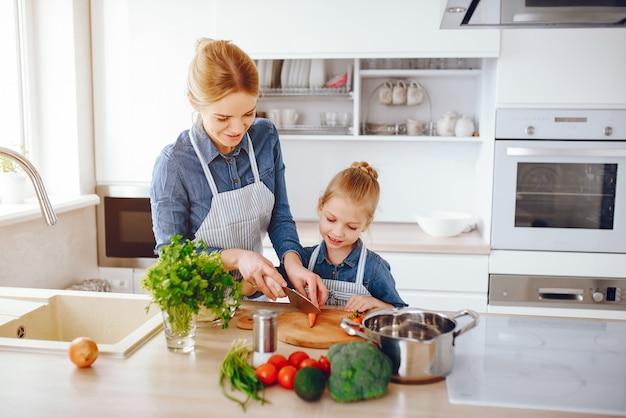 Linda mãe de camisa azul e avental está preparando uma salada de vegetais frescos em casa Foto gratuita
