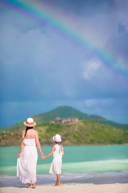 Linda mãe e filha na praia do caribe com incrível arco-íris Foto Premium