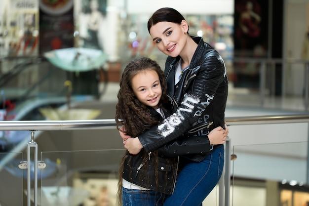 Linda mãe e filha sorrindo enquanto fazia compras no shopping Foto Premium