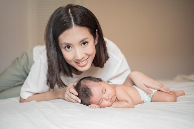 Linda mãe está brincando com seu bebê recém-nascido no quarto. Foto Premium