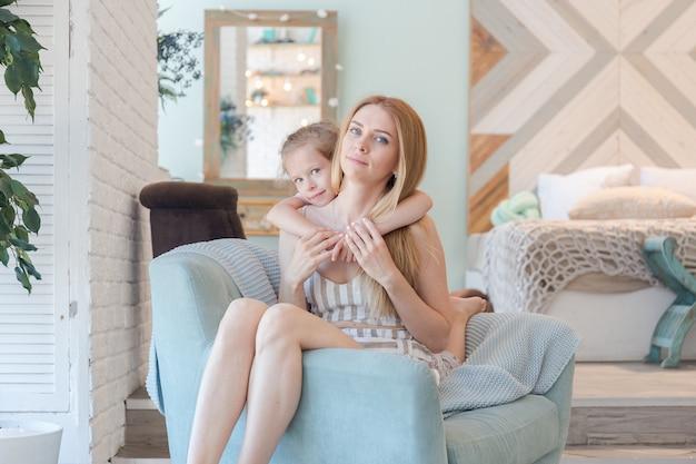 Linda mãe loira e linda filha se divertindo e brincando em um apartamento moderno com um design elegante Foto Premium