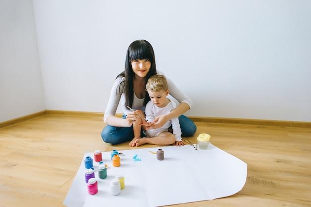 Linda mãe, seu filho e gato pintando no papel Foto Premium