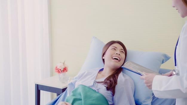 Linda médica asiática inteligente e paciente discutindo e explicando algo com a área de transferência Foto gratuita