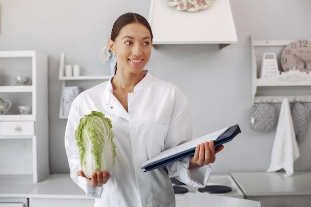 Linda médica em uma cozinha com legumes Foto gratuita
