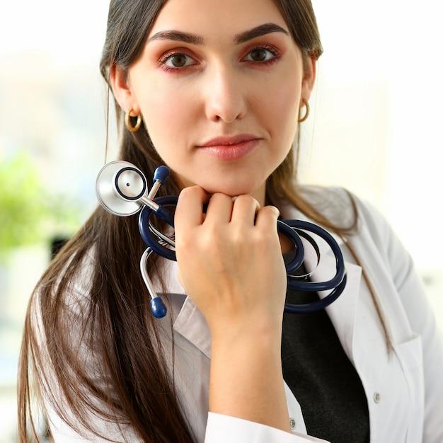 Linda médica sorridente sente-se no local de trabalho Foto Premium
