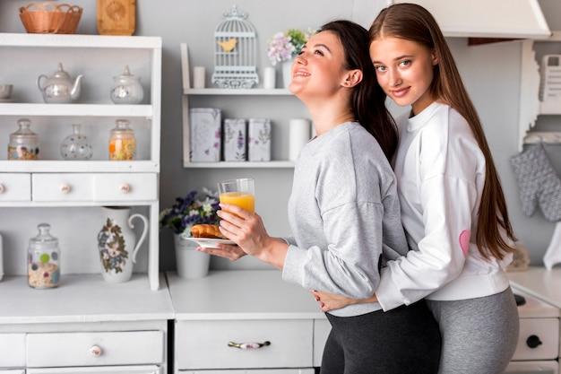 Linda menina adolescente abraçando outro, mantendo o suco Foto gratuita