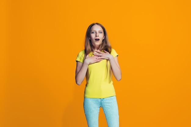 Linda menina adolescente olhando surpreso isolado na laranja Foto gratuita