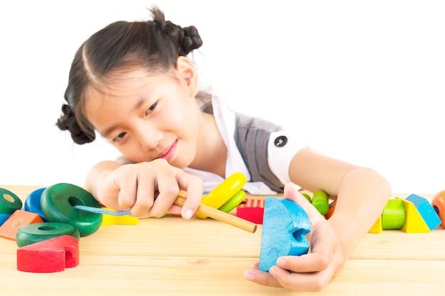 Linda menina asiática é jogar brinquedo colorido bloco de madeira Foto gratuita