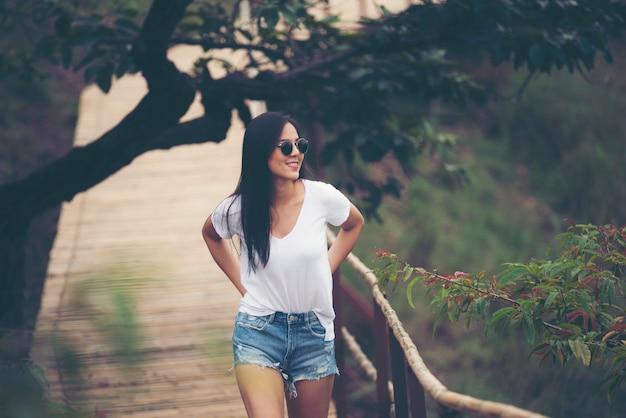 Linda menina asiática sorri no jardim, conceito de natureza ao ar livre Foto Premium