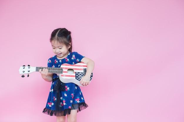 Linda menina asiática tocando guitarra na cor rosa com espaço de cópia Foto Premium