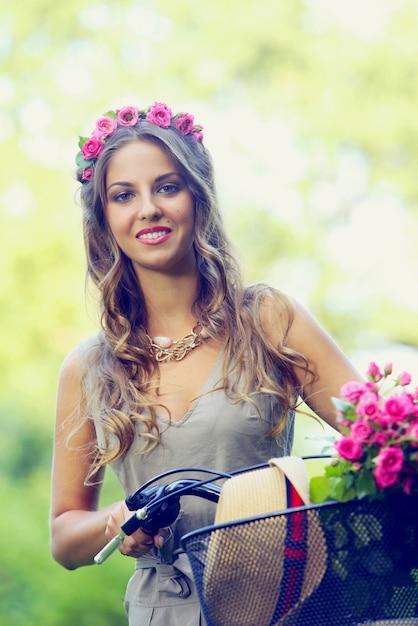 Linda menina com flores em uma bicicleta Foto gratuita
