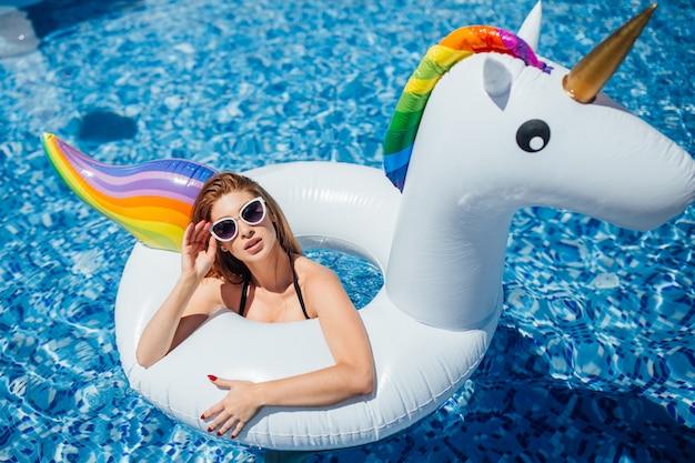 Linda menina com uma bela figura está descansando e banhos de sol em uma piscina Foto Premium