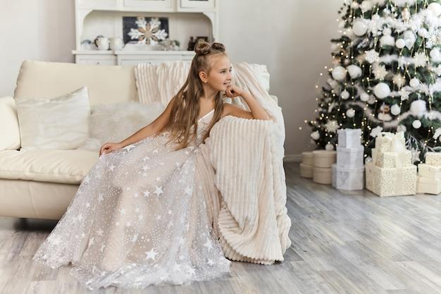 Linda menina com vestido festivo no interior de natal Foto Premium