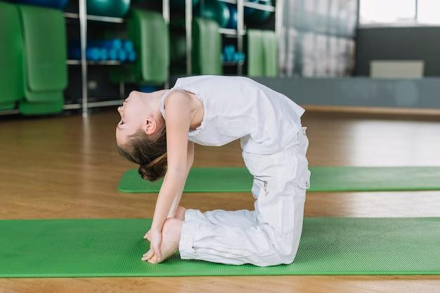 Linda menina criança praticando camelo pose no ginásio Foto gratuita
