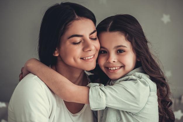 Linda menina da escola e a mãe dela estão abraçando e sorrindo. Foto Premium