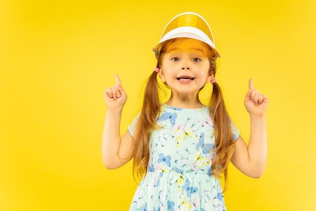 Linda menina emocional isolada em amarelo Foto gratuita