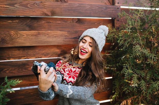 Linda menina morena com chapéu de inverno, fazendo selfie retrato na câmera no exterior de madeira. Foto gratuita