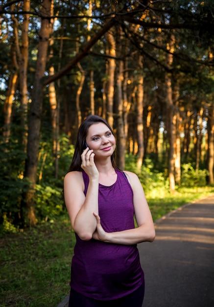 Linda menina morena falando ao telefone no parque ao pôr do sol Foto Premium