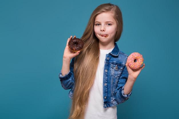 Linda menina na jaqueta jeans com longos cabelos castanhos segurar doughnust Foto Premium