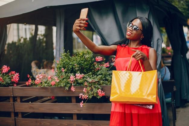 Linda menina negra com sacos de compras em uma cidade Foto gratuita