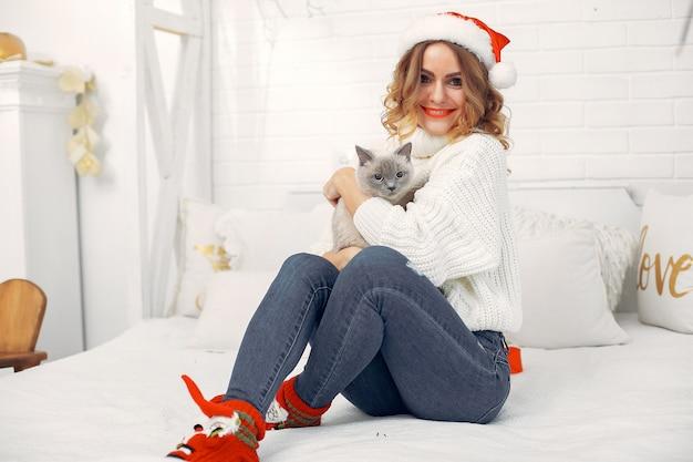 Linda menina sentada em uma cama com gatinho fofo Foto gratuita
