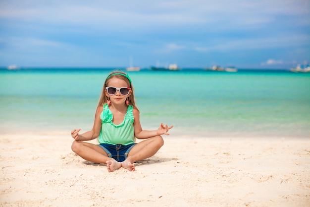 Linda menina sentada em uma posição de lótus em uma praia exótica Foto Premium