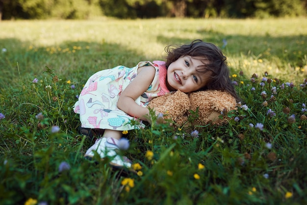 Linda menina sorridente, abraçando o urso macio de brinquedo Foto gratuita