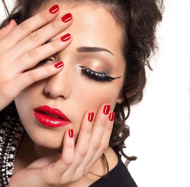 Linda modelo com unhas vermelhas, lábios e maquiagem criativa nos olhos - isolada na parede branca Foto gratuita