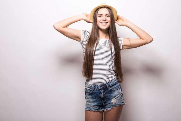 Linda modelo feminina mantém a mão no chapéu de palha, usa top branco com ombros nus, parece com expressão confiante, isolada sobre parede branca Foto gratuita