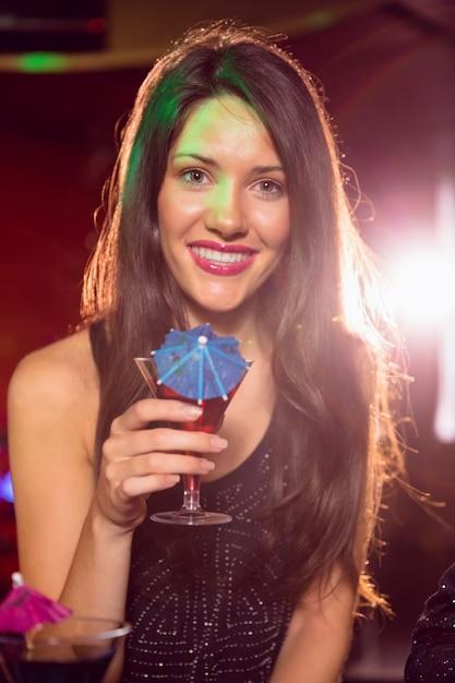 Linda morena bebendo um coquetel Foto Premium