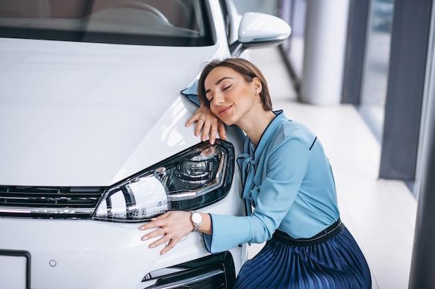 Linda mulher abraçando um carro Foto gratuita