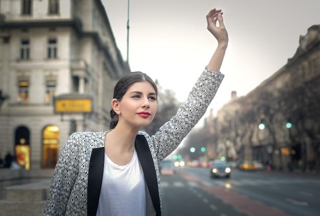 Linda mulher acenando na cidade Foto Premium