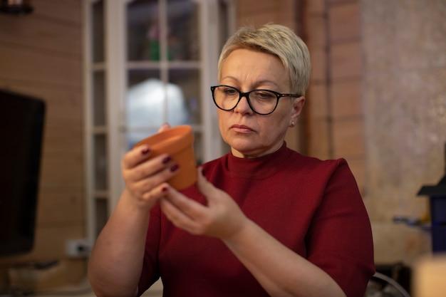 Linda mulher adulta segurando um pote de cerâmica de barro nas mãos Foto Premium